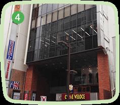 旧中山道を進むと、道路反対側に茶色の柱と窓ガラスが特徴的なビルが見えます。「ワールドウィングさいたま」は当ビルの5階になります。             ※1階には「CAFE VELOCE」さんの看板がございます。